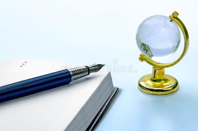Notebook and pen, globe royalty free stock images