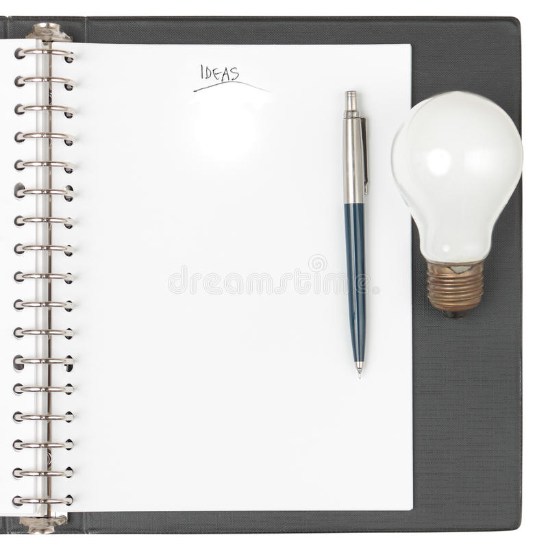 Notebook with pen and light bulb stock photography