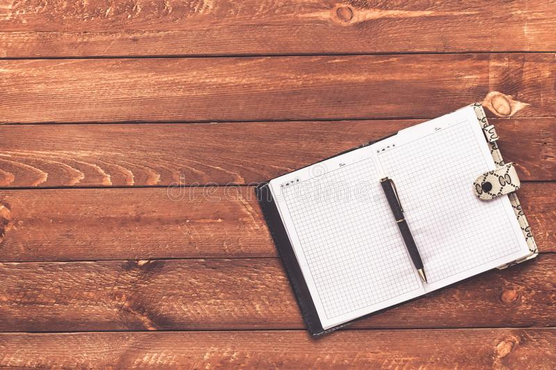 Notebook with pen on old wooden table stock photography