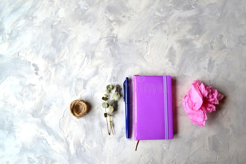 Notebook, pen,pencil,flower, eucalyptus, scissors on the textured table. stock photo