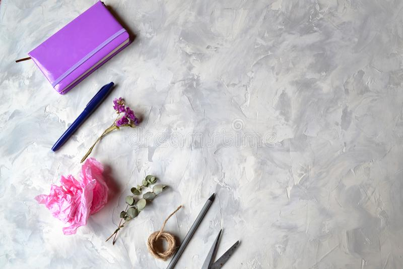 Notebook, pen,pencil,flower, eucalyptus, scissors on the textured table. stock image