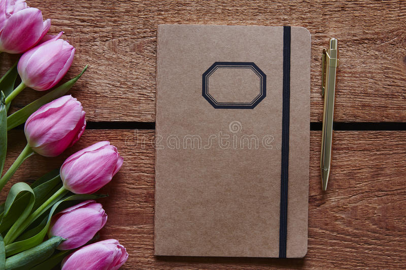 Notebook and pen spring atmosphere with pink tulips royalty free stock photos