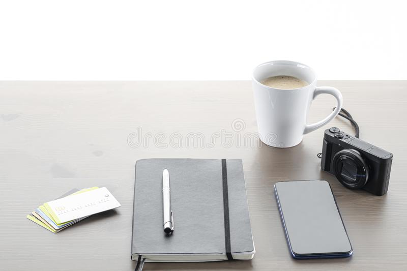 A notebook with a pen on top, payment cards, a mobile phone, a camera and a cup of coffee with milk on a wooden table with a white royalty free stock images