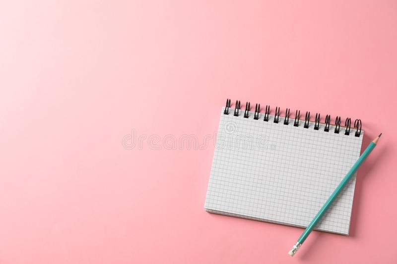 Notebook and pencil on color background stock images
