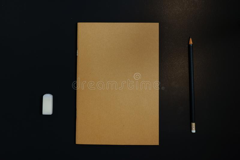 Notebook, pencil and eraser on black background royalty free stock photos