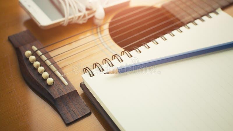Notebook and pencil on guitar, Writing music. Book stock photos