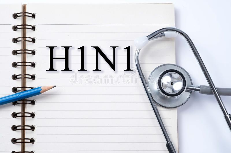 Notebook, pencil and stethoscope with words H1N1 diseases. royalty free stock photography