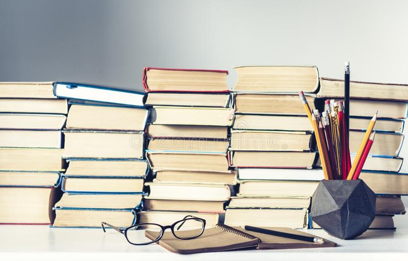 Notebook, pencils, glasses and stack of books, school background for education learning concept stock image