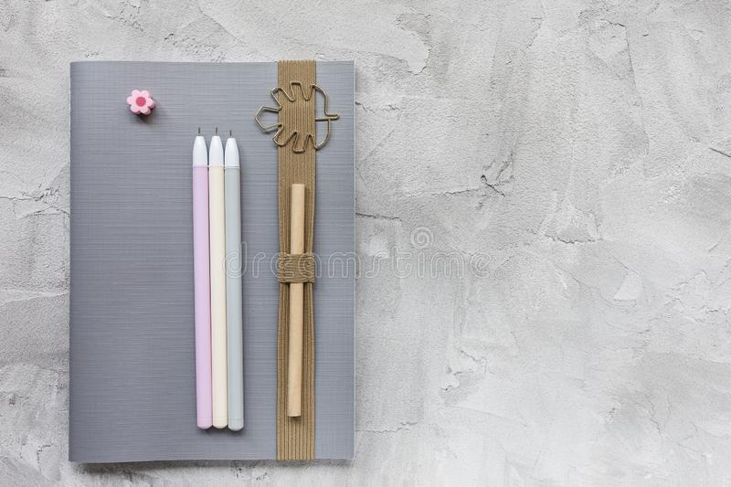 Notebook and pens on a gray background. Notebook, pencil and pens on a gray background. Education, back to school or studying concept, flat lay, top view, social royalty free stock photos