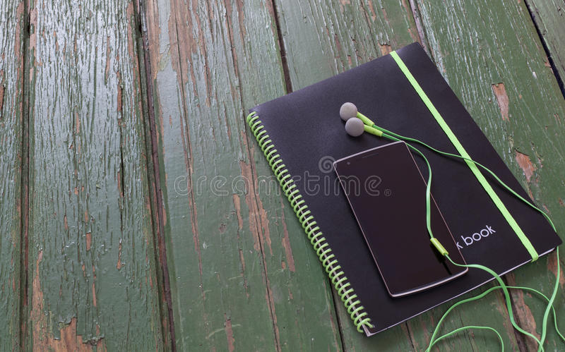 Notebook and phone with headphones on green wood table stock image