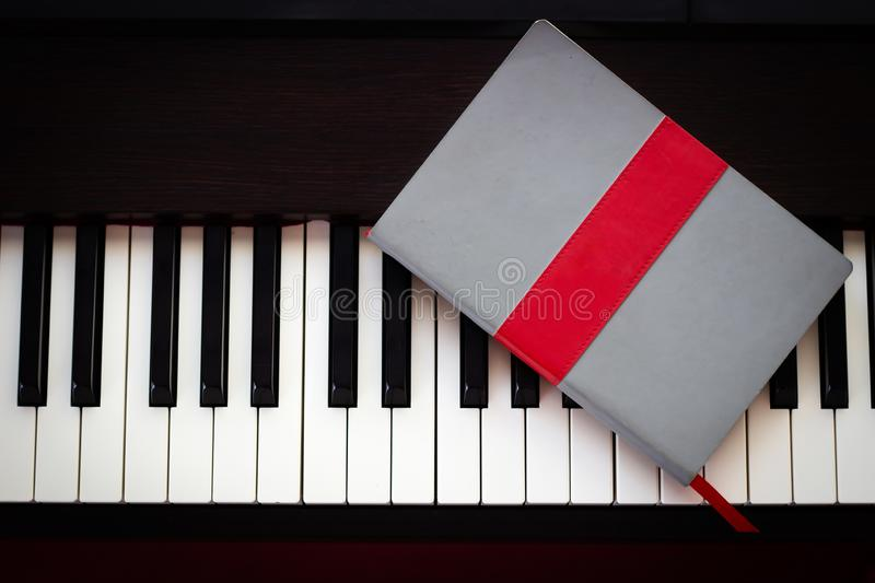 Notebook on piano key. Top view with copy space. Concept of take a note of song, abstract, acoustic, art, background, black, brown, classic, classical, close stock photography