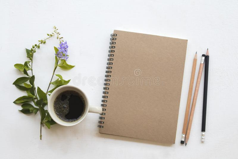 Notebook planner for business work and coffee. Notebook planner for business work with hot black coffee ,flower decoration flat lay style on background white royalty free stock images