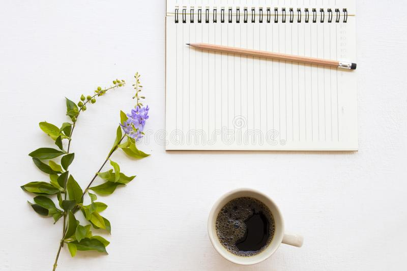 Notebook planner for business work and coffee. Notebook planner for business work with hot black coffee ,flower decoration flat lay style on background white royalty free stock image