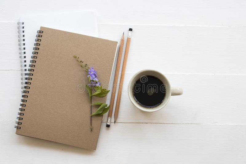 Notebook planner for business work and coffee. Notebook planner for business work with hot black coffee ,flower decoration flat lay style on background white stock photography