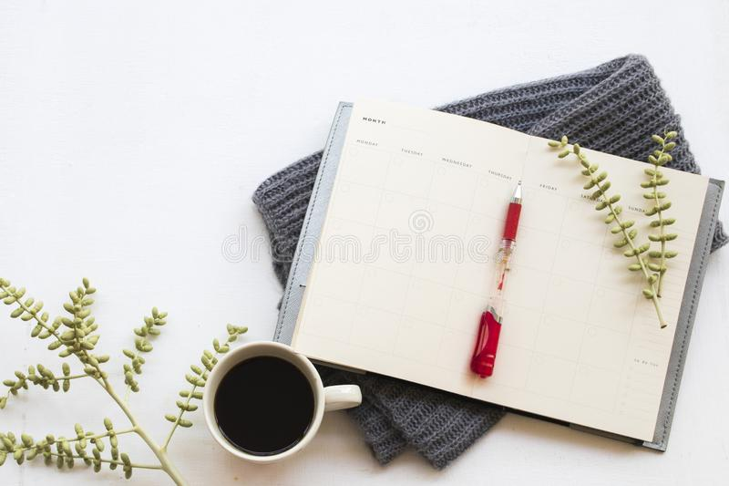 Notebook planner for business work at office desk. Notebook planner for business work with knitting wool scarf of lifestyle woman in winter season on background stock images