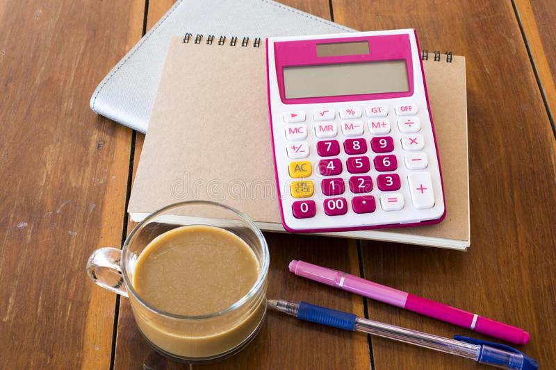 Notebook planner ,calculator for business work. With hot coffee decoration on table at office desk royalty free stock image