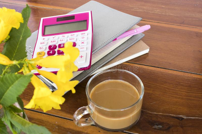 Notebook planner ,calculator for business work. With hot coffee decoration on table at office desk stock photo