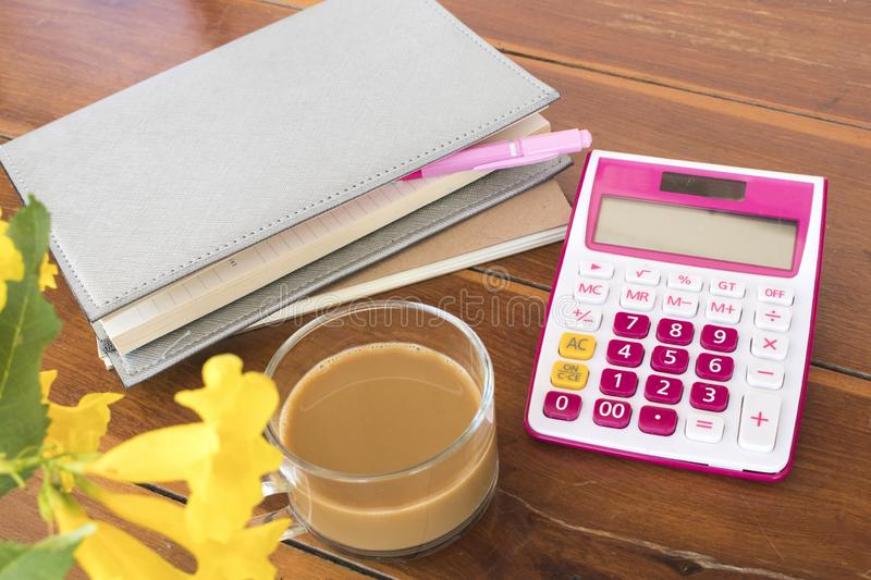 Notebook planner ,calculator for business work. With hot coffee decoration on table at office desk royalty free stock photo