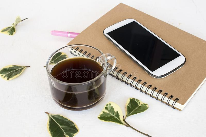Notebook planner ,mobile phone for business work at office desk. Notebook planner ,mobile phone for business work with hot coffee arrangement flat lay style on royalty free stock photos
