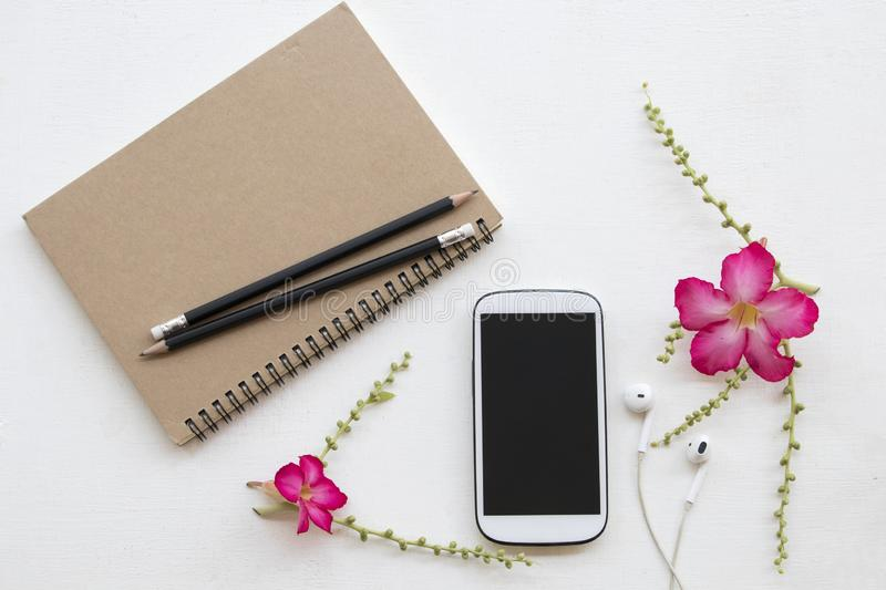 Notebook planner and mobile phone for business work. With pink flower decoration flat lay style on background white stock photography