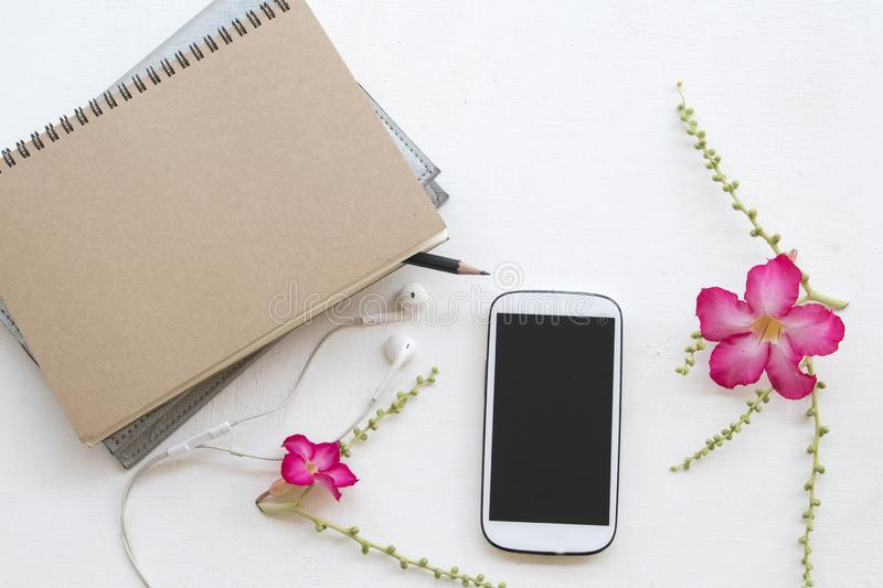 Notebook planner and mobile phone for business work. With pink flower decoration flat lay style on background white royalty free stock images