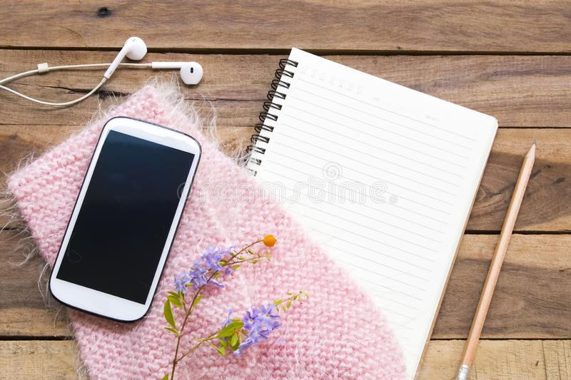 Notebook planner ,mobile phone and earphone for business work with pink knitting wool scarf of lifestyle woman royalty free stock image