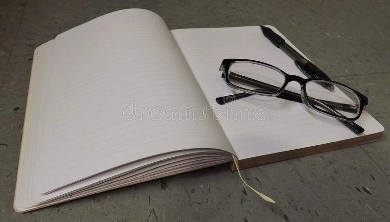 Notebook with reading glasses and pen on top stock photos
