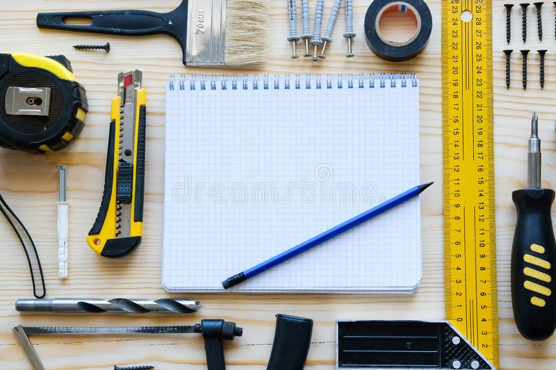 Notebook for records and construction tools for building a house or apartment renovation, on a wooden table. The workplace of the stock photography