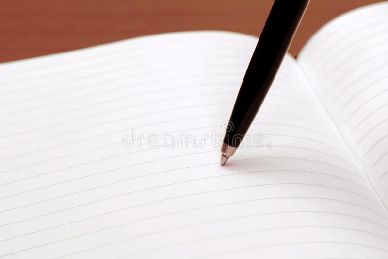 Notebook with recycle paper and ball point pen on work table. Copy space for text, macro close up background stock photography