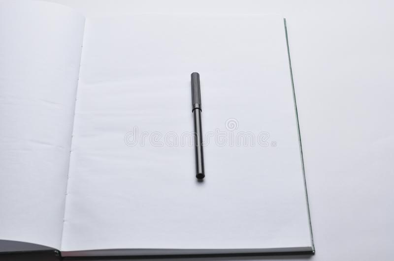 A notebook and a red and black pen  on a white background.Copy space. Template diary open desktop cover write creative pad document journal close view business royalty free stock image