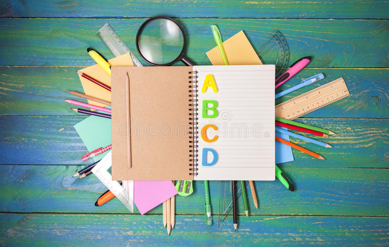 notebook with school supplies on blue wood background,concept ba royalty free stock photo