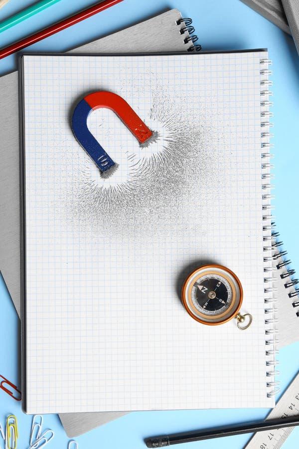 Notebook, Schreibpapier, Kompass und Magnet mit Eisenpulver auf blauem Hintergrund stockfotografie