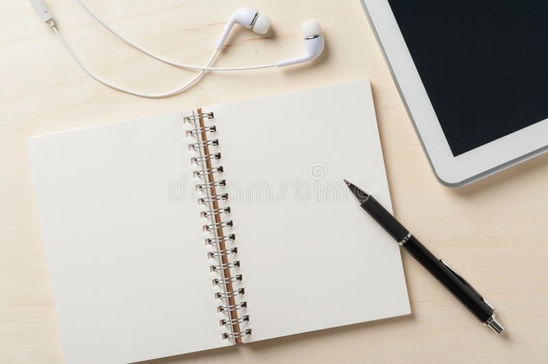 Notebook beside small tablet pc. Notebook with blank area for text or message and pen beside small tablet pc and in ear headset on wood table royalty free stock images