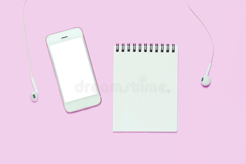 Notebook and smartphone with head phones on pink background. stock image