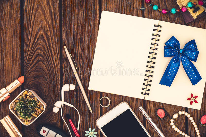Notebook, smartphone, note book with white pages and women accessories are lying on wooden background. Stuff for business. Blank Notebook, smartphone, note book royalty free stock images
