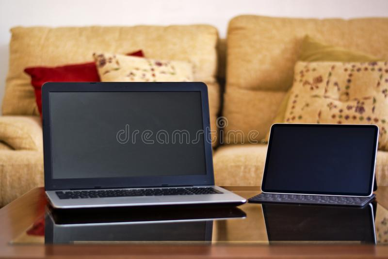 A notebook and a tablet on a wooden and glass table. This in a room, behind you can see an armchair with cushions. Technological concept royalty free stock images