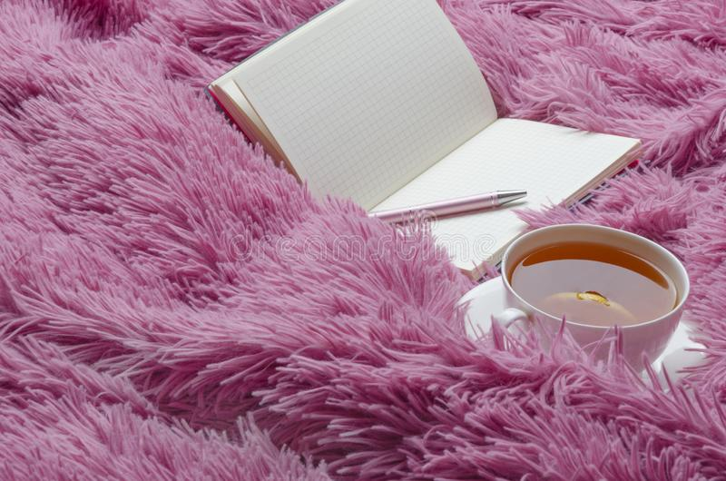 Notebook,tea with lemon on bright pink blanket.Relax and planning time. Notebook,tea with lemon on bright pink blanket.Relaxation and planning above,abstract royalty free stock images