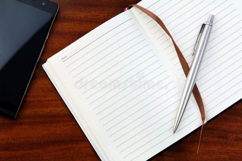 Notebook, telephone and ball-point pen. Green notebook with stamping sign of the telephone and ball-point pen stock images