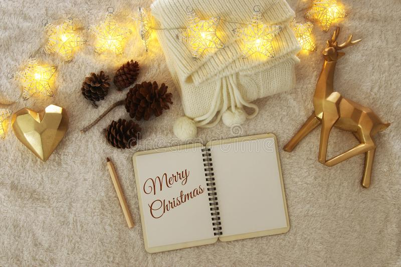 Notebook with text: MERRY CHRISTMAS and cup of cappuccino over cozy and warm fur carpet. Top view. stock images
