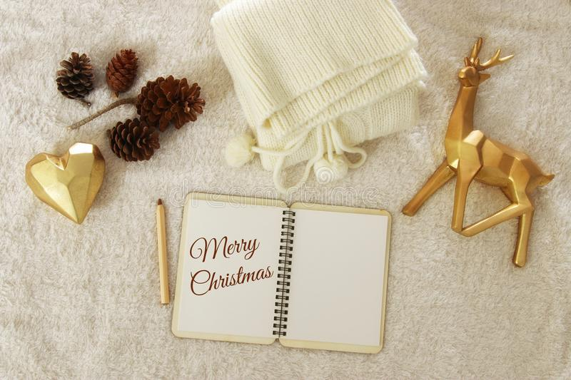 Notebook with text: MERRY CHRISTMAS and cup of cappuccino over cozy and warm fur carpet. Top view. royalty free stock photography