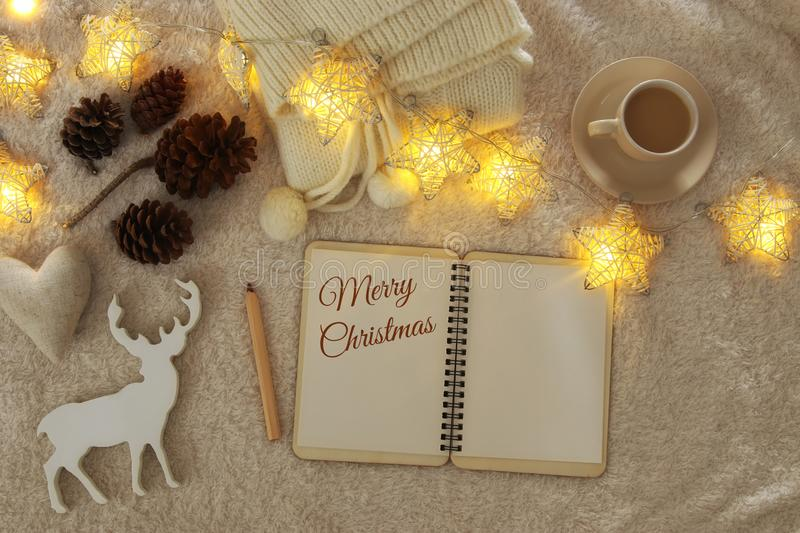 Notebook with text: MERRY CHRISTMAS and cup of cappuccino over cozy and warm fur carpet. Top view. royalty free stock image