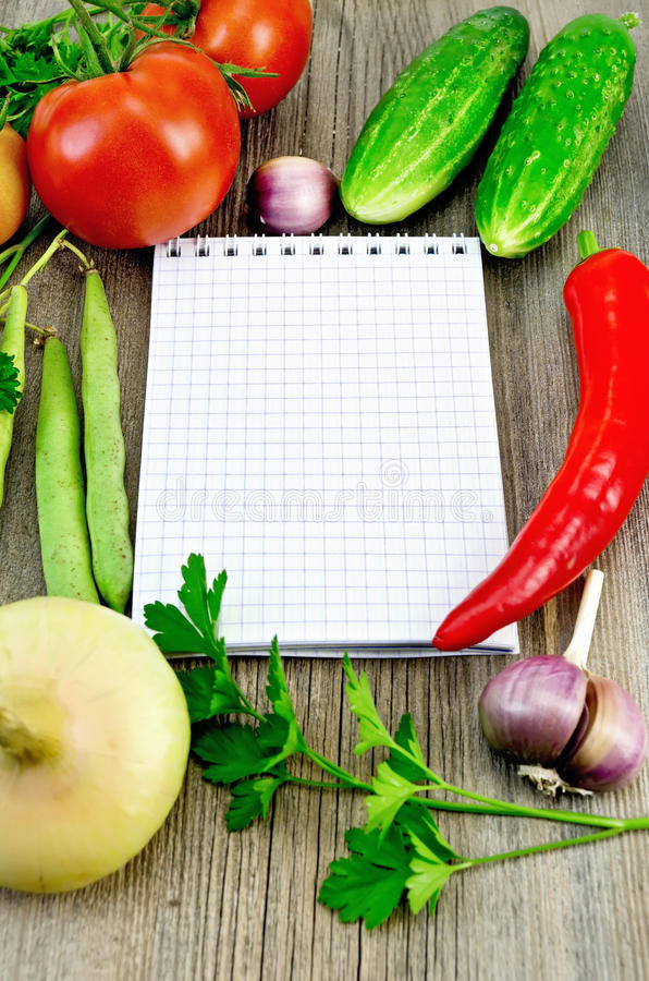 Notebook with vegetables and pepper royalty free stock photography