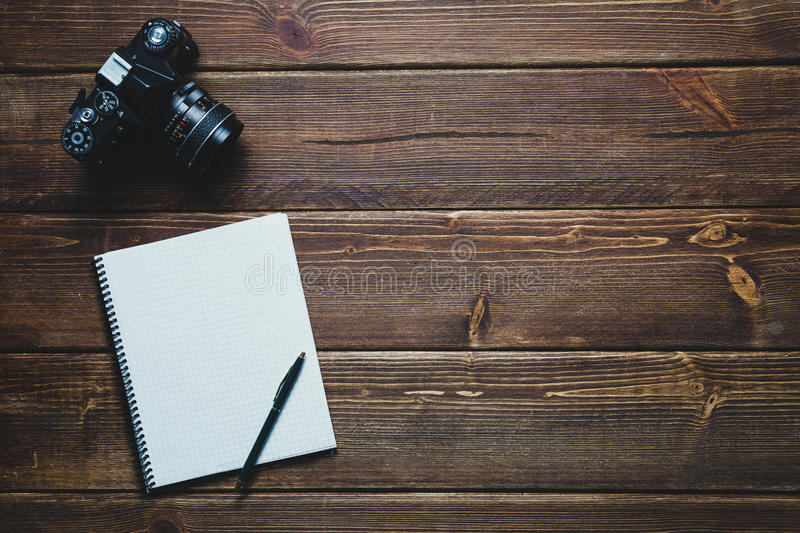 Notebook and vintage camera on the desk stock image