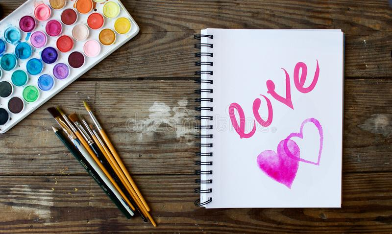 Notebook with watercolor hearts and love word. Paint brushes and notebook on a wooden table, with two watercolor hearts and watercolor love painted , valentine`s stock images