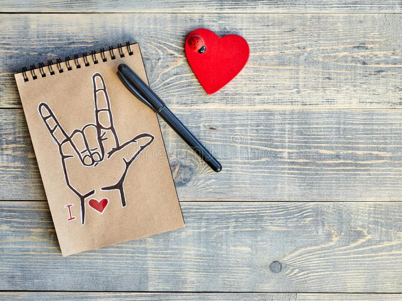 Notebook of Kraft paper, which is painted with an old black marker, the symbol of ASL American Sign Language ILY and a wooden royalty free stock photography