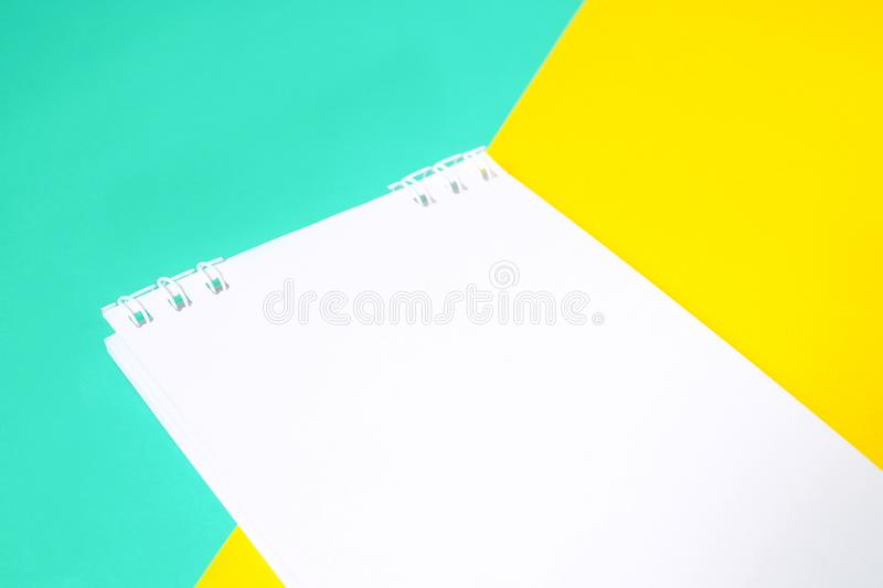 Notebook with white paper on multi-colored background With yellow and blue stock image