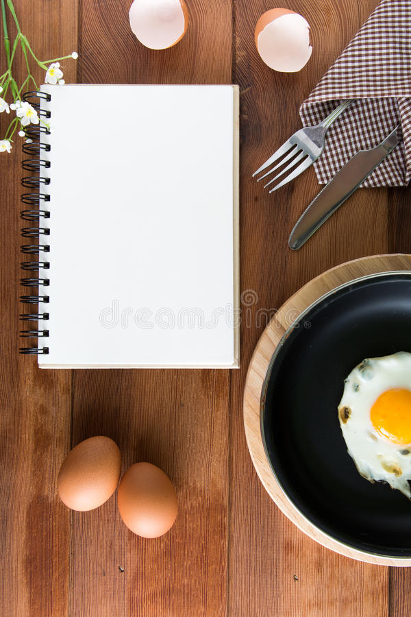 Notebook white on a wooden floor with egg royalty free stock photo