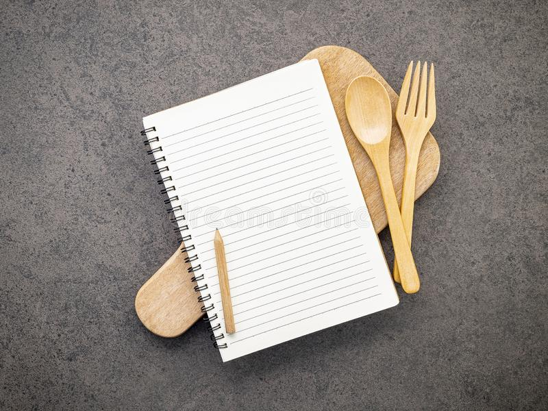 Notebook with wooden spoon set up on dark stone background stock image
