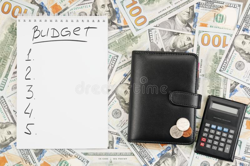 Notebook with the word Budget and a list of targets, wallet, coins, calculator on the background of dollar bills royalty free stock photos