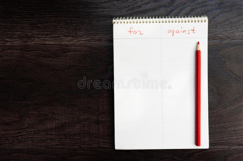 A notebook with the words `for` and `against`, and a red pencil lie on a wooden surface. The concept of analysis and choice stock photos
